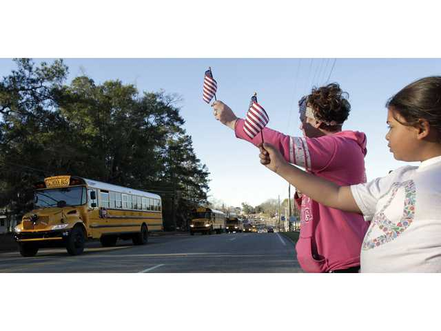 Kiya Buchanan, right, and Raechel Buchanan, left, hold up flags as the funeral procession for Charles Albert Poland Jr., passes by.