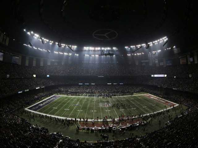 Fans and members of the Baltimore Ravens and San Francisco 49ers wait for power to return in the Superdome during an outage.