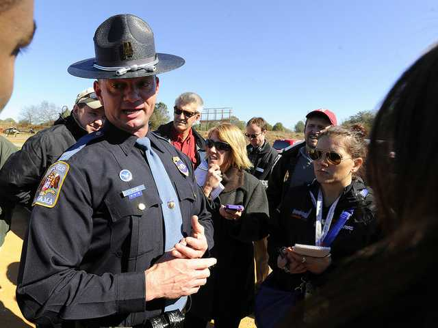 Alabama state trooper Kevin Cook, center, speaks to media, Saturday, in Midland City, Ala.