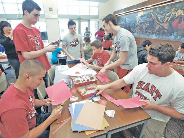 "Hart football players Gabriel Salcedo, left, and Erik Stafford, right, join their teammates as they make Valentine's Day cards for the troops as part of the ""Hearts for Heroes"" event held at the Newhall Library on Saturday. (Dan Watson/The Signal)"