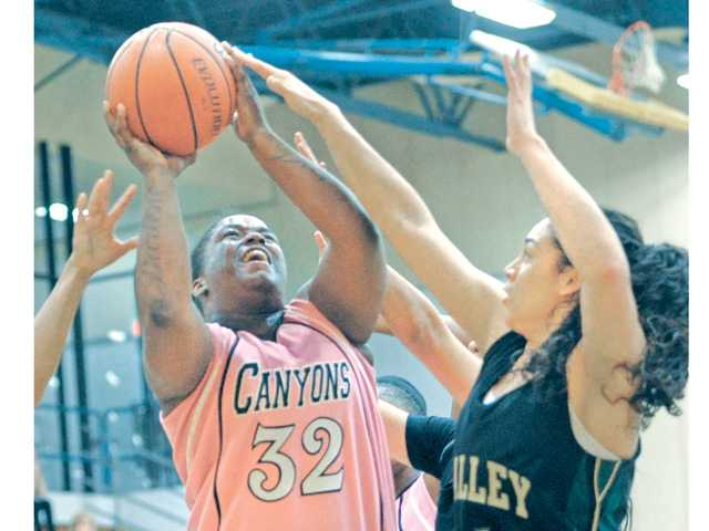 College of the Canyons' Keiona Mathews (32) scores agaisnt L.A. Valley College defender Annie Avanessian (4) and Bobbie Morgutia (24) at COC on Saturday.