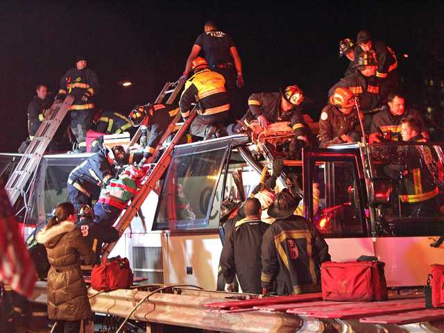 Emergency personnel remove passengers at the scene of a bus crash, Saturday.