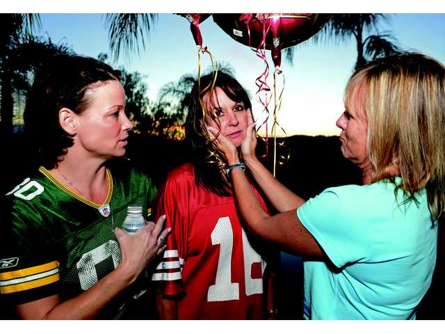 Amy Spadoni, in green, looks on as Heidi Young shows sympathy for 49ers fan and party hostess Rory Mang after the Ravens scored on a 108-yard  run to open the 3rd quarter of the game.