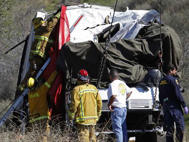 A firefighter adjusts a tarp to cover a victim inside after a tow truck lifted a tour bus back onto the road Monday, after it collided with two other vehicles and crashed Sunday, killing at least eight people and injuring 38, on Highway 38 just north of Yucaipa. (AP)