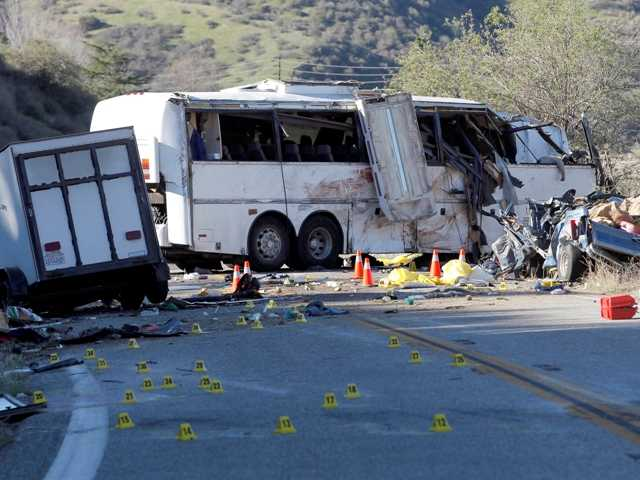Evidence markers dot the road in front of the wreckage of a tour bus in the Southern California mountains near San Bernardino Monday.