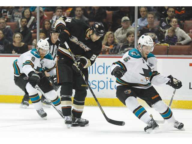 Anaheim Ducks center Daniel Winnik, center, controls the puck as two San Jose Sharks defend on Monday in Anaheim.