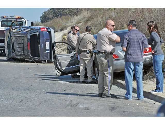 California Highway Patrol officers investigate a two-car crash on the shoulder of northbound Highway 14 south of Golden Valley Road in Canyon Country on Tuesday. (Jonathan Pobre/The Signal)