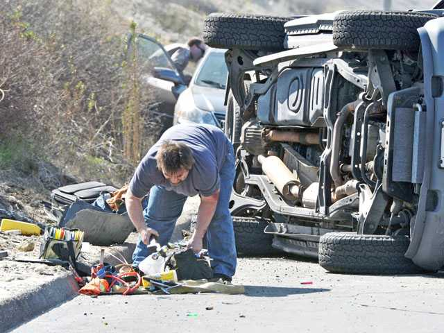 A man gathers belongings in front of an overturned Ford Explorer at the scene of a crash on northbound Highway 14 near Golden Valley Road in Canyon Country on Tuesday.
