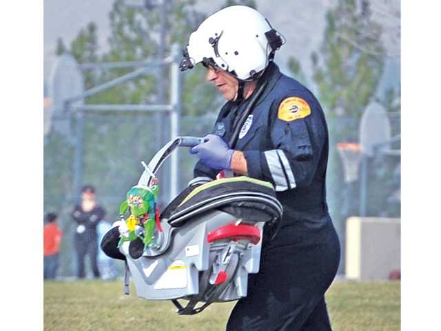 Los Angeles County firefighter/paramedic Brian Clayton carries a baby boy in his car seat to a waiting helicopter to be airlifted to a Los Angeles hospital on Tuesday. Signal photo by Dan Watson