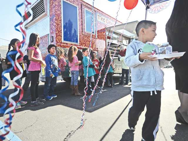 "Second- and third-grade students line up for a special lunch from the Santa Clarita Valley School Food Services Agency's ""Cruisin Cafe"" mobile lunch truck, which visited Canyon Springs Community School on Friday as a schoolwide incentive for the K-sixth students for their recent proficiency in math and English language arts. (Dan Watson/The Signal)"
