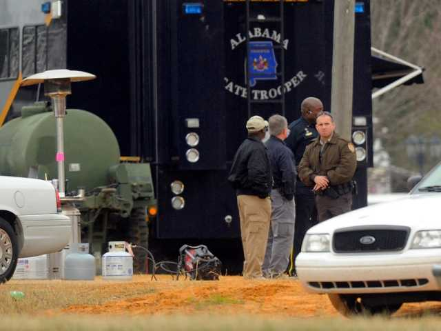 FBI and other personnel process the crime scene in Alabama Tuesday,a day after a police raid left Jimmy Lee Dykes dead. Dykes held a a 5-year-old boy hostage for a week.