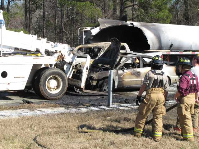 Firefighters stand by as a forklift moves a smashed and burned car at the scene where 27 vehicles collided Wednesday.