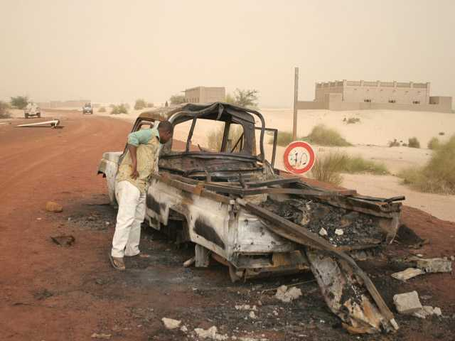 In this photo taken Thursday Jan. 31, 2013, a man takes a close look at a burned-out truck in Timbuktu, Mali.