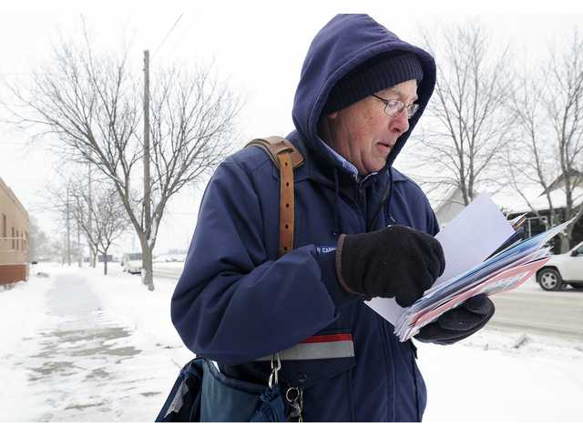 Mail carrier Bruce Nicklay walks along East Third Street in Winona, Minn.