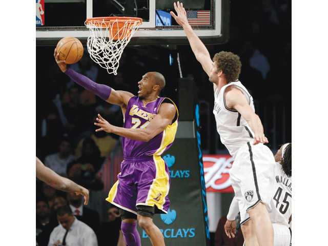 Los Angeles Lakers guard Kobe Bryant, left, puts up a shot underneath the basket while Brooklyn Net Brook Lopez defends on Tuesday in New York.