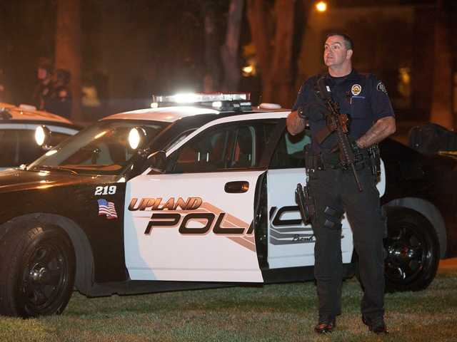 Police respond in Riverside early Thursday morning after one officer was killed and another critically wounded in a shoot out with a murder suspect.