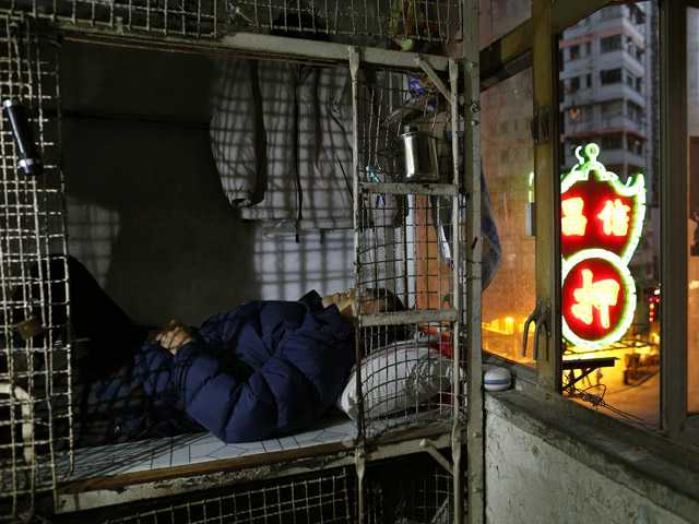 62-year-old Cheng Man Wai lays in his cage, measuring 1.5 square meters (16 square feet), which he calls home.