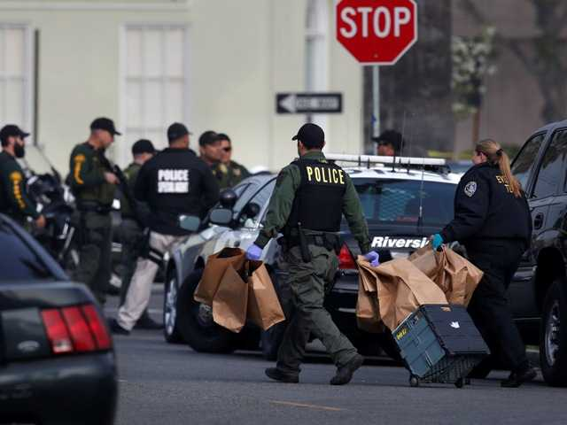 Police carry evidence bags near the area where Christopher Dorner is a suspect in a Riverside shooting, Thursday. Police are now looking at a burned pickup truck on a mountain road.
