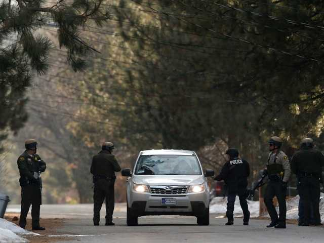 San Bernardino County sheriff's deputies search a car in Big Bear on Thursday. An ex-Los Angeles police officer who authorities say went on a killing spree set off a manhunt that stretched across three states and into Mexico. Associated Press photo.