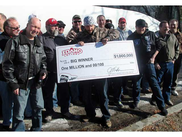 John Polidori, a member of a group of 34 University of Utah maintenance workers who won $1 million in the Idaho Lottery, poses with a ceremonial check.