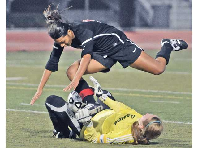 Hart High's Jenny Chavez, top, collides with Canyon goalkeeper Meghan Kennedy, bottom, in final seconds of the first half at Canyon High School on Thursday. Hart won 2-0.