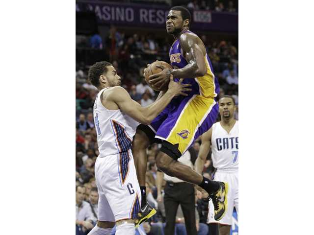 Los Angeles Lakers' Earl Clark, right, is fouled by Charlotte Bobcats' Jeffery Taylor, left.