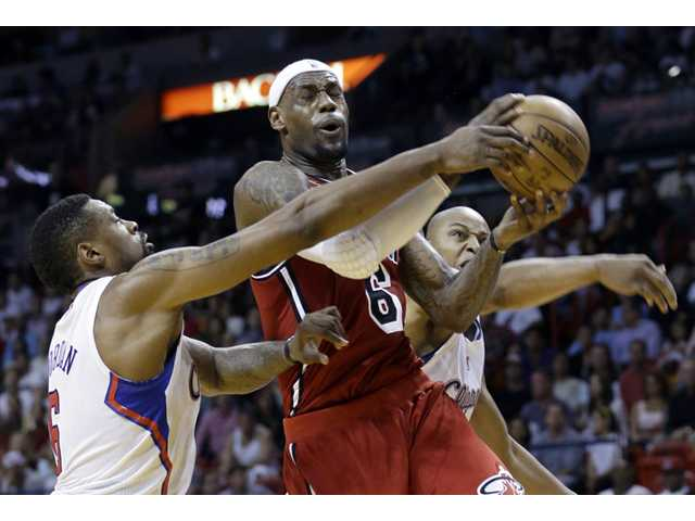 Miami Heat's LeBron James (6) is fouled as he goes to the basket by Los Angeles Clippers' DeAndre Jordan.