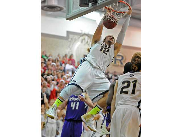West Ranch center Ako Kaluna (12) dunks in the second half of a game against Valencia on Friday at West Ranch School.