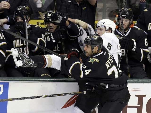 Anaheim Ducks defenseman Ben Lovejoy (6) is knocked into the Dallas Stars bench by Stars left wing Eric Nystrom (24).