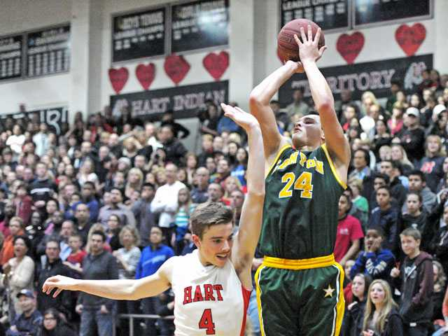 Canyon forward Park Mackenzie sets up a 3-pointer as Hart's Andrew MacArthur quickly closes in to defend in the fourth quarter on Friday night at Hart High.