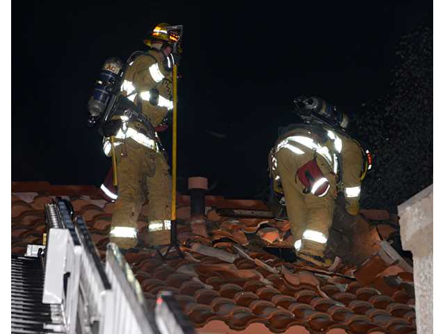 Firefighters work on the roof of a home in Newhall early today. PHOTO BY RICK MCCLURE/FOR THE SIGNAL