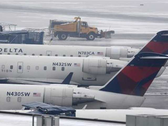 A truck with a plow drives pass Delta planes parked at their gates at the Salt Lake City Airport Thursday, Jan. 24, 2013. The Salt Lake City International Airport was closed due to icy conditions. A Frontier airplane slid on the runway during landing Thursday morning, but nobody was injured.