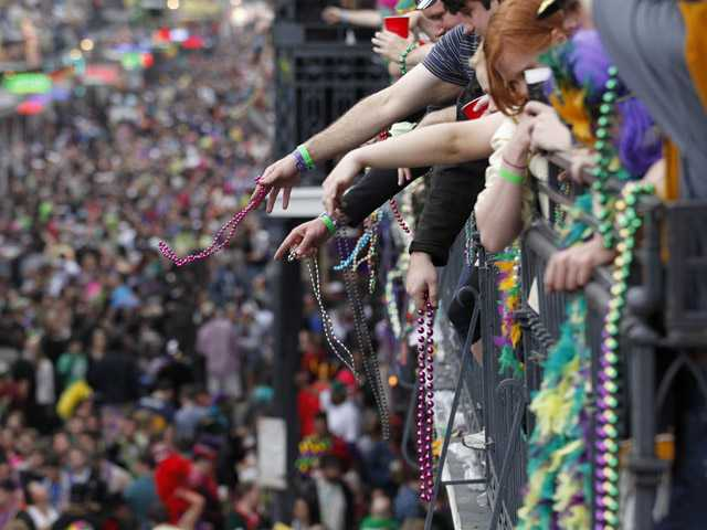 Revelers throw beads from the balcony of the Royal Sonesta Hotel onto crowds on Bourbon Street during Mardi Gras Day festivities.