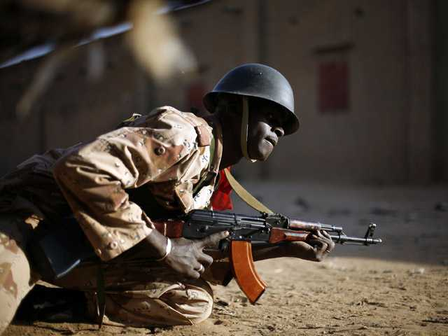 A Malian soldier takes cover behind a truck during exchanges of fire with jihadists in Gao, northern Mali.