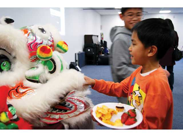 Seven-year-old Levin Lam, a student at the the Santa Clarita Valley Chinese School, checks out the ceremonial head of a dragon at the Chinese New Year celebration Sunday.