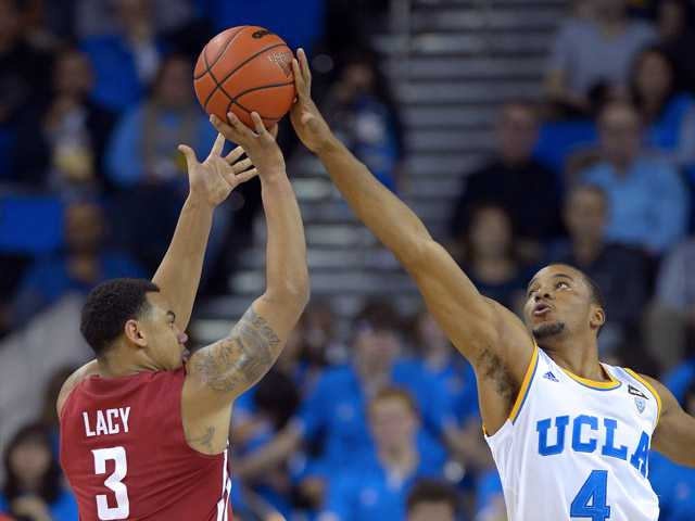 UCLA guard Norman Powell, right, blocks a shot by Washington State guard DaVonte Lacy during the second half Saturday in Los Angeles.