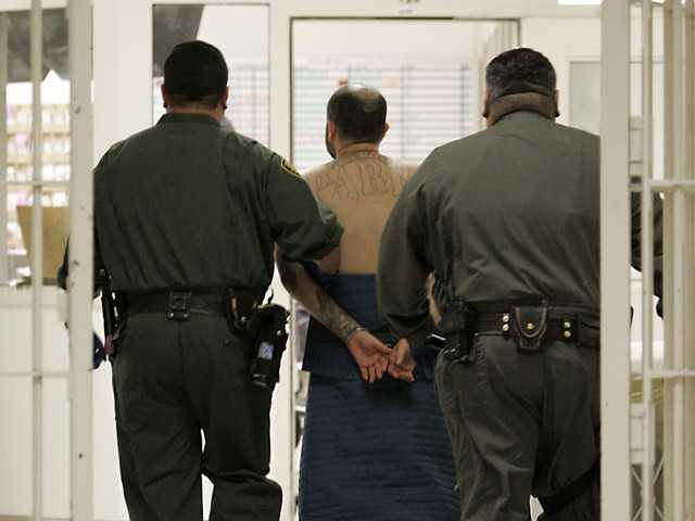In this Jan. 14, 2009 file photo, an inmate on suicide watch is escorted by correctional officers at the California Substance Abuse Treatment Facility in Corcoran. (AP)