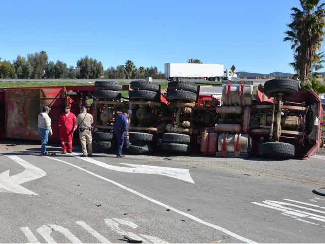 CHP officers and L.A. County firefighters inspect big rig that overturned on the southbound Interstate 5 off-ramp to Lake Hughes Road in Castaic on Monday. One person was injured. Photo by Rick McClure