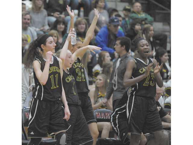 Canyon High players celebrate during Canyon's 71-29 victory over Hart on Friday at Hart High School.