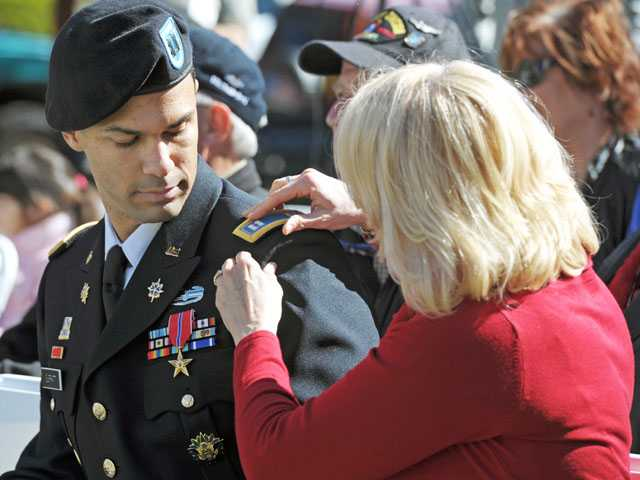 Kacey Surratt straightens the shoulder mark of her son, Army Capt. Gabriel Surratt, after he is promoted Monday during a ceremony in Newhall. Signal photo by Jonathan Pobre