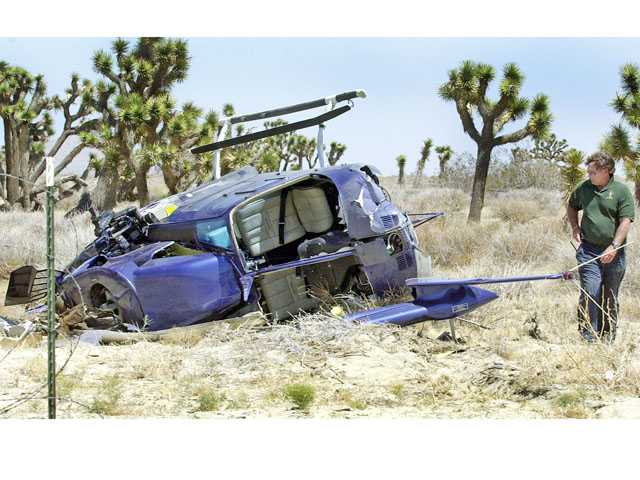 Pilot David Gibbs looks over the wreckage from a 2004 helicopter crash in Palmdale. He and two passengers walked away uninjured in that crash. Courtesy Antelope Valley Press/Evelyn Kristo