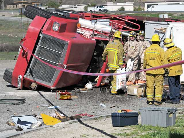 Firefighters and a hazardous materials crew work the scene where a big rig flipped over and blocked freeway ramps near Interstate 5 at Lake Hughes Road in Castaic on Monday.