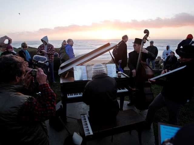 People listen and take pictures of Mauro Ffortissimo and his friends playing music at sunset in Half Moon Bay on Feb. 8. The grand piano, on its last legs, sits on a bluff.