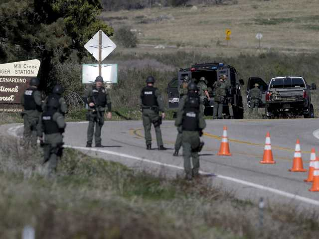 Law Enforcement personnel gear up along Hwy 38 during the hunt for accused killer and fired Los Angeles police officer, Christopher Dorner.