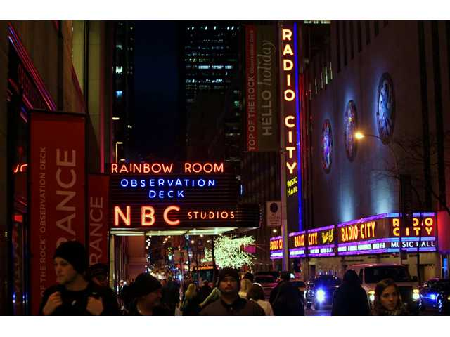 In this 2009 photo, the NBC logo glows in neon lights among other iconic signs at its headquarters in New York.