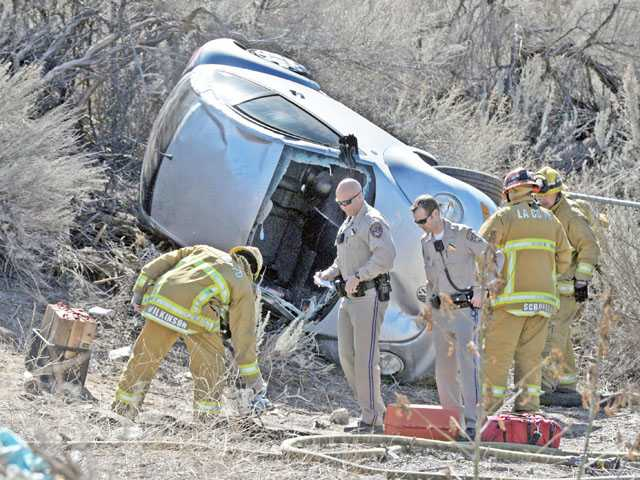 California Highway Patrol officers and firefighters work a scene where a Volkswagen rolled over off Vasquez Canyon Road near Sierra Highway in Canyon Country on Tuesday.