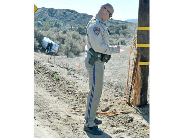 A California Highway Patrol officer takes notes near a pole damaged by a crash on Vasquez Canyon Road near Sierra Highway in Canyon Country on Tuesday.