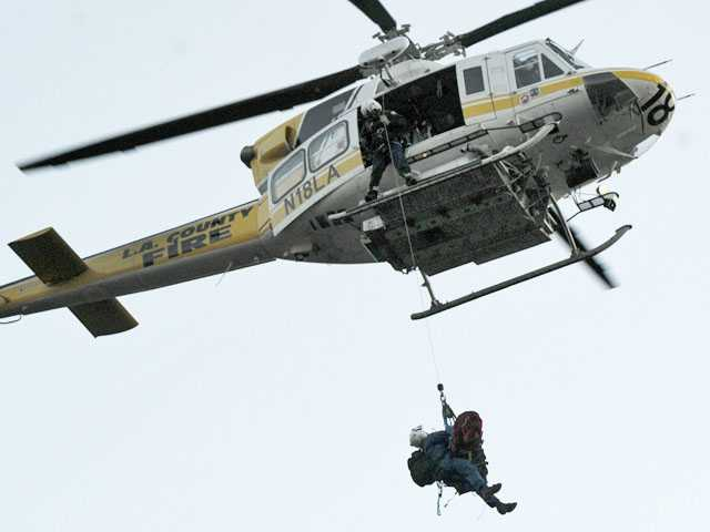 A 57-year-old man is hoisted by a Los Angeles County firefighter-paramedic into a helicopter to be transported to a hospital after he was rescued from his vehicle off Sand Canyon Road in the Angeles National Forest on Tuesday. (Jonathan Pobre/The Signal)