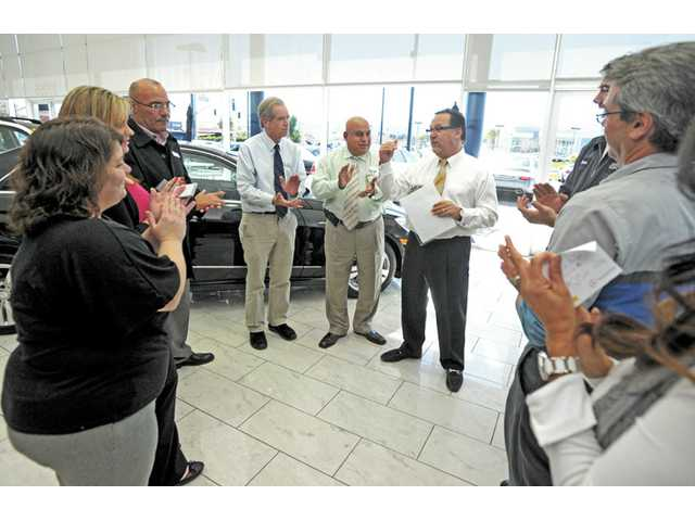 Owner and general manager Michael Sage, center right, leads a meeting in the showroom at Mercedes-Benz of Valencia.