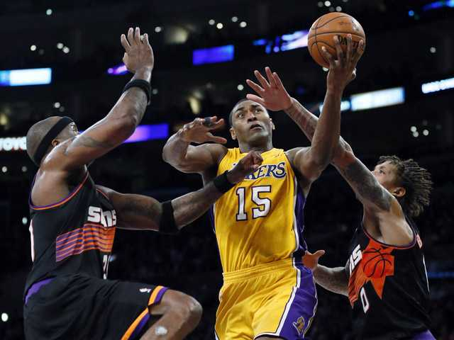 Los Angeles Laker Metta World Peace, center, is fouled by Phoenix Sun Michael Beasley, right, as Sun Jermaine O'Neal, left, also defends on Tuesday in Los Angeles. The Lakers won 91-85.